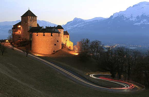 Cars drive past Vaduz Castle in capital Vaduz, Liechtenstein.