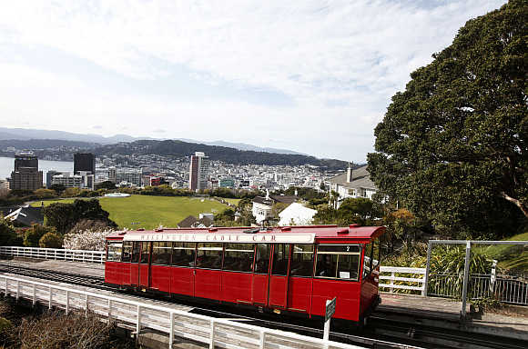 Wellington Cable Car ascends with a view of the city in the background, New Zealand.