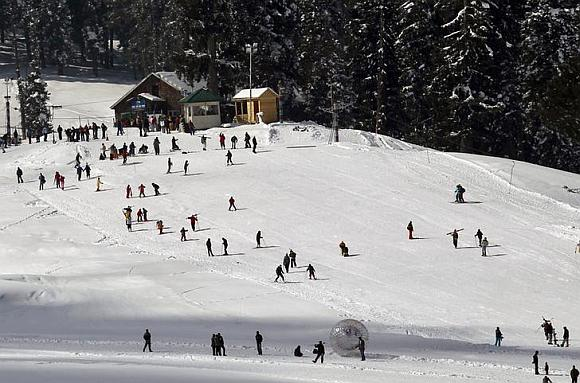 Tourists and skiers ski on a slope in Gulmarg, 55 km (34 miles) west of Srinagar.