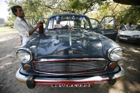 A driver stands next to his parked Ambassador car, manufactured by Hindustan Motors, in Kolkata.