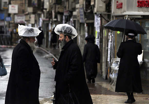 Ultra-Orthodox Jews, wearing hats covered with plastic against the rain, talk in Jerusalem's Mea Shearim neighbourhood, Israel.