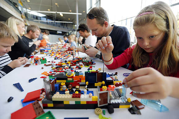 Helene Haga, right, her father Trond, centre, and her brother Henrik, left, attend the annual Lego Festival in Oslo, Sweden.