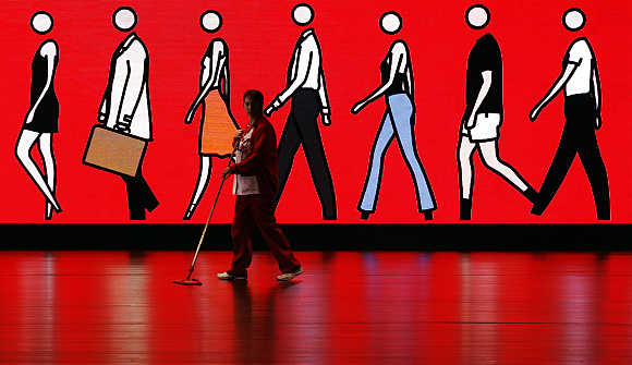 A cleaner sweeps the floor as she walks past an illuminated sign depicting people walking, at Spain's Santander headquarters in Boadilla del Monte outside Madrid.
