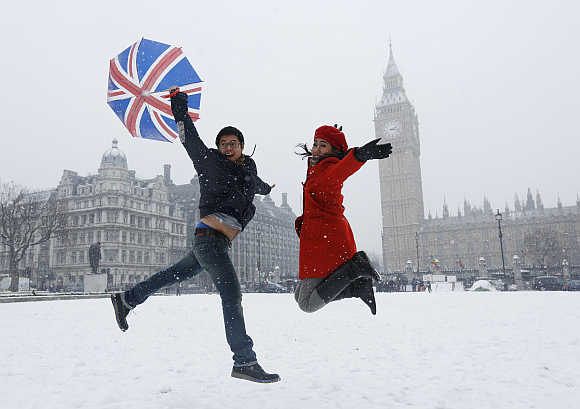 Pandu and Dian, tourists from Indonesia, jump for a souvenir photograph taken by their friend in front of the Houses of Parliament in central London.