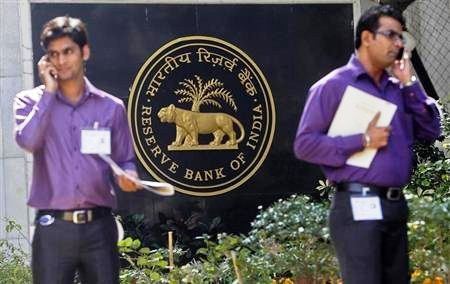 Two men make phone calls while standing near a Reserve Bank of India crest at the RBI headquarters in Mumbai.