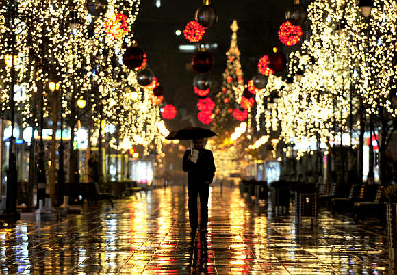 A man walks near trees illuminated with Christmas lights in Skopje, Macedonia.