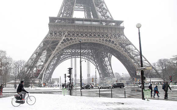 A man rides a bicycle as he makes his way along a snow-covered sidewalk near the Eiffel Tower in Paris, France.