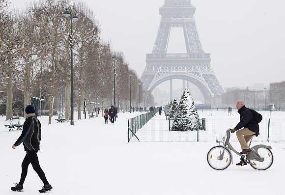 A man rides Velib, a self-service public bicycle, as he makes his way along a snow-covered area at the Champs de Mars near the Eiffel Tower in Paris, France.