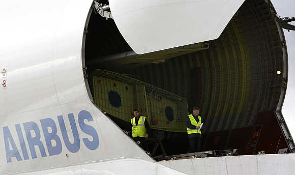 Workers check the first pair of wings for a new tanker aircraft after they were loaded onto a Beluga transport plane in North Wales, Great Britain.