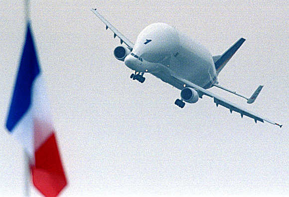 Airbus Beluga, the largest cargo plane in the world, flies near the French flag at the Paris Air Show.