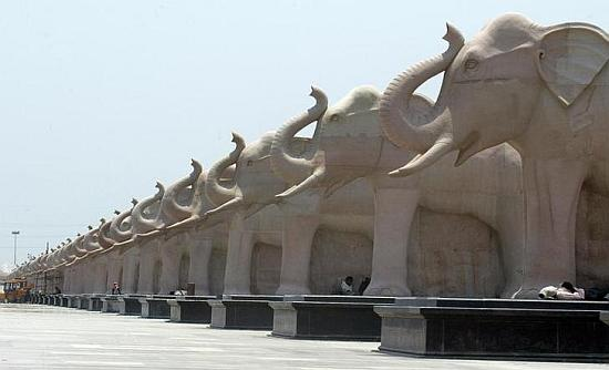 Labourers rest under elephant statues made of stone inside the Ambedkar memorial park in Lucknow.