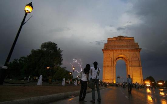 Girls watch lightning striking over the India Gate in New Delhi.