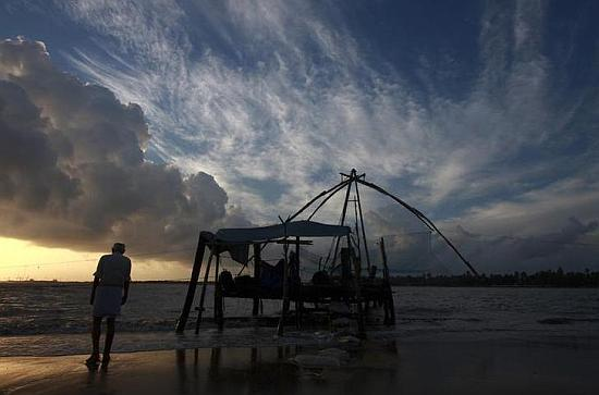 An elderly man strolls on a beach with the backdrop of monsoon clouds, as sun sets in Kochi.