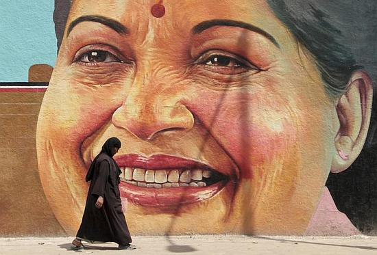A woman walks past a portrait of J. Jayalalithaa, Chief Minister of the southern Indian state of Tamil Nadu, in Chennai.