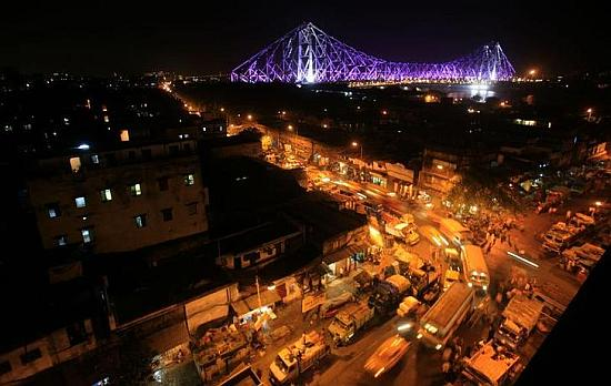 Traffic moves during the evening as the Howrah Bridge is lit up in the background in Kolkata.