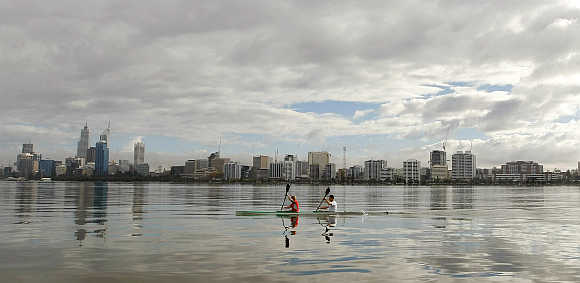 Kayakers paddle on the Swan River past the Perth city skyline in Australia.