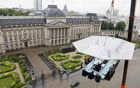 Guests enjoy a 'Dinner in the Sky' on a platform hanging in front of the Royal Palace in Brussels, Belgium.