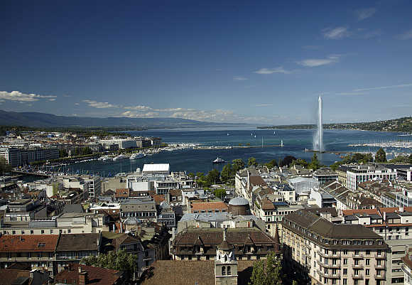 An overview picture shows the Jet d'Eau (water fountain) and the Lake Leman from the St-Pierre Cathedrale in Geneva, Switzerland.
