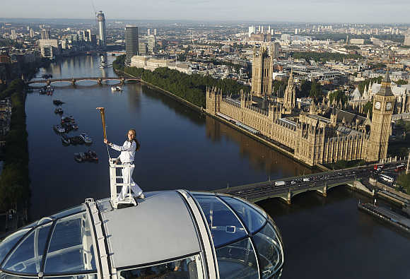 Torch bearer Amelia Hempleman-Adams, 17, stands on top of a capsule on the London Eye as part of the torch relay ahead of the London 2012 Olympic Games in London, United Kingdom.