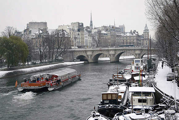 A 'bateaux mouches' tourist boat makes its way up the River Seine in Paris, France.