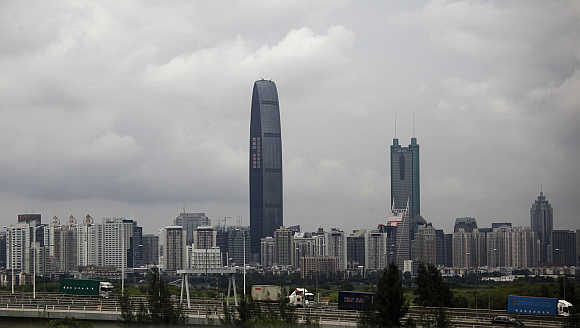 Container trucks cross a bridge in front of the 100-floor Kingkey 100, the tallest building in downtown Shenzhen, China.