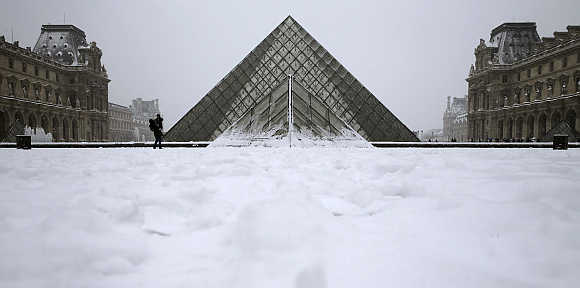 People enjoy the snow in front of Paris landmark, the Pyramid of the Louvre Museum, in France.