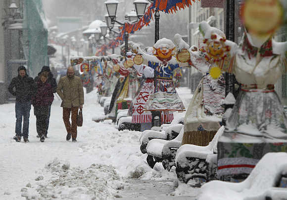 People walk past traditional Maslenitsa spring festival decorations during a snowstorm in Moscow, Russia.