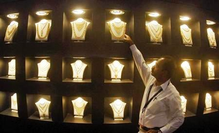 An employee displays gold necklaces at the 'Gem and Jewellery India International Exhibition 2010' (GJIIE) in Chennai.