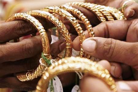 A woman holds gold bangles at a jewellery shop in Kolkata.