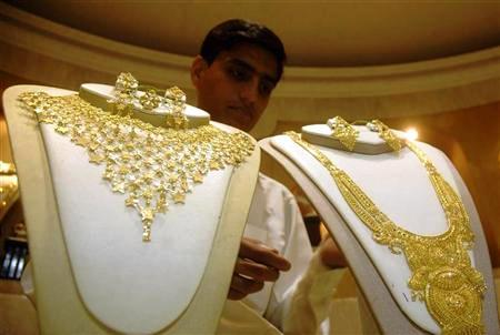 A salesman arranges gold necklaces at a jewellery shop in Agartala.