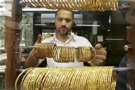 A Jordanian goldsmith holds gold bracelets at his shop in Amman.