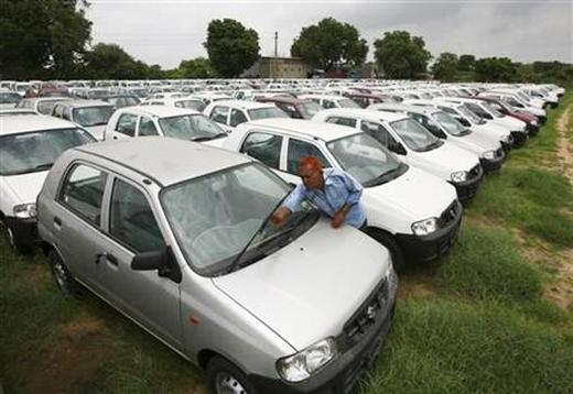 A worker adjusts the windscreen wipers of a parked Alto car at a Maruti Suzuki stockyard.
