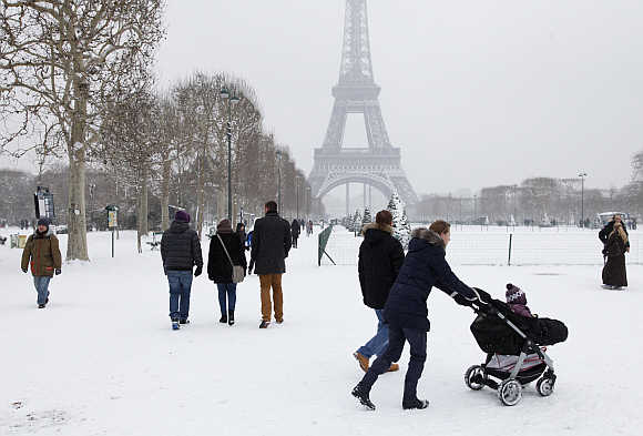 People walk in groups on a snow-covered path near the Eiffel Tower in Paris, France.