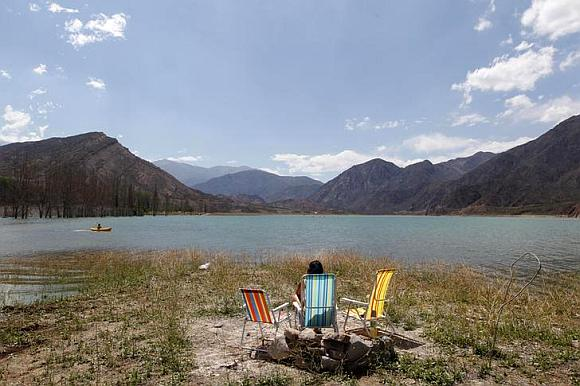 A tourist enjoys the view from the edge of the lake of the Potrerillos district.