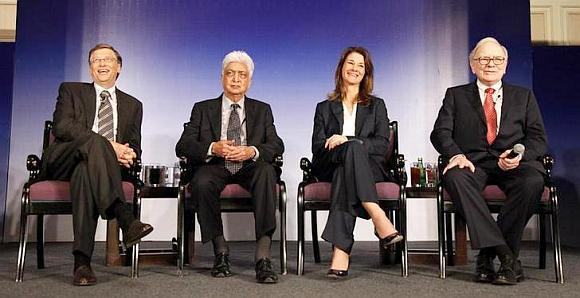 Bill Gates (L) his wife Melinda Gates, Azim Premji (2nd L) and billionaire Warren Buffett (R) attend a news conference.
