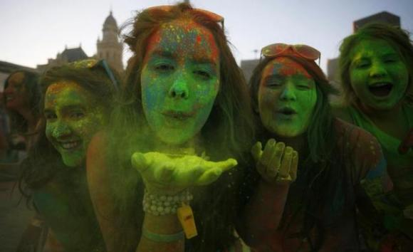 Revellers blow coloured cornflour powder as they take part in the Holi festival.