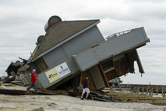 Men inspect damage to a beach club destroyed by Hurricane Sandy in Sea Bright, New Jersey, United States.