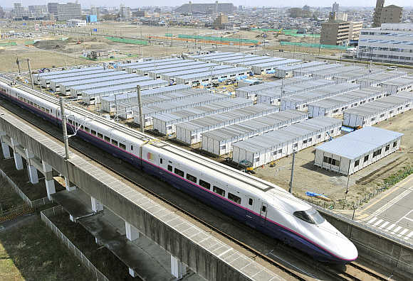 Shinkansen, or bullet train, speeds past temporary houses for survivors of the earthquake and tsunami in Sendai, Miyagi prefecture, Japan.