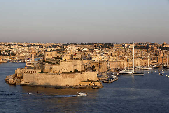 A boat sails past the medieval Fort Saint Angelo in Vittoriosa in Valletta's Grand Harbour, Malta.