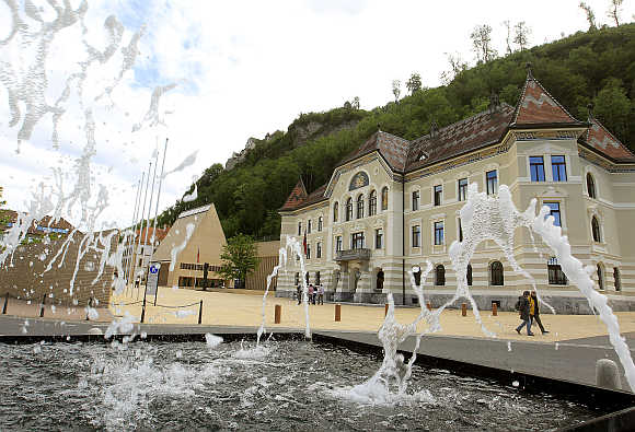 People walk past the government building, right, and the Landtag parliament, left, in Liechtenstein's capital Vaduz.