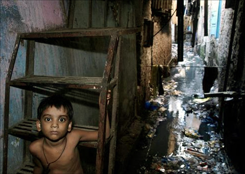 A child sits on the steps of stairs at a slum in Mumbai.