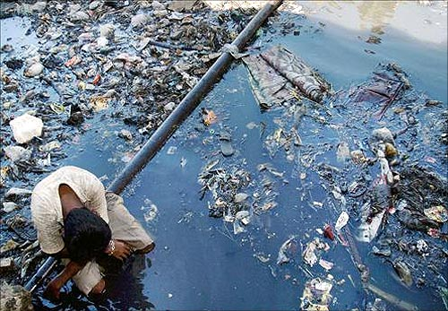 A boy rests on a pipe in a canal flowing through the slums in Mumbai.