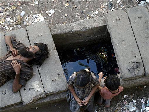 A man sleeps on a gutter cover as children play in a slum in Mumbai.