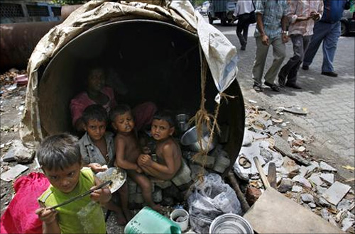 Children eat in their his make-shift home in an unused waterpipe at a street in Mumbai.