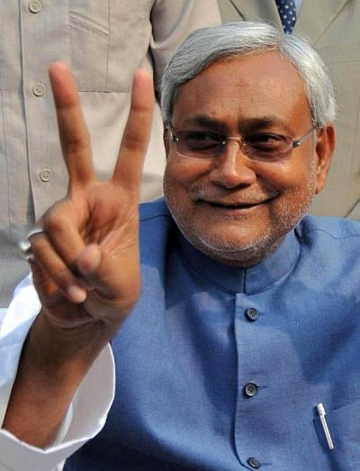 Bihar Chief Minister Nitish Kumar flashes a V-sign during a news conference
