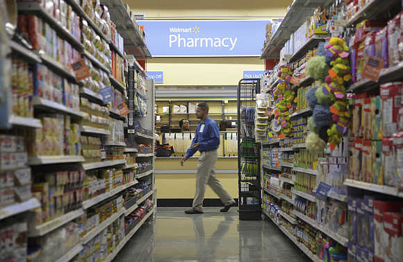 A worker walks past a pharmacy in Walmart Express store in Chicago.