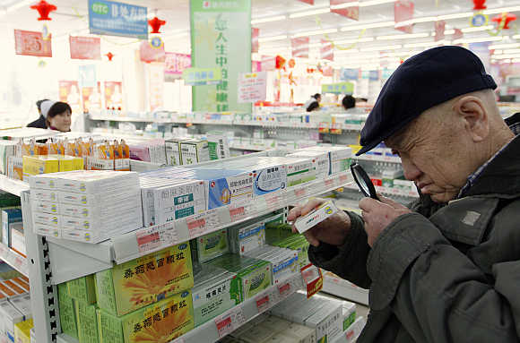 A man uses a magnifier to see the descriptions on a pack of medicine at a pharmacy in Dandong, Liaoning province, China.