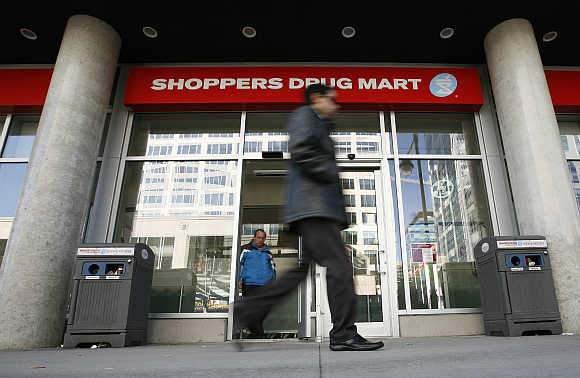 A pedestrian walks past a Shoppers Drug Mart in Ottawa, Canada.