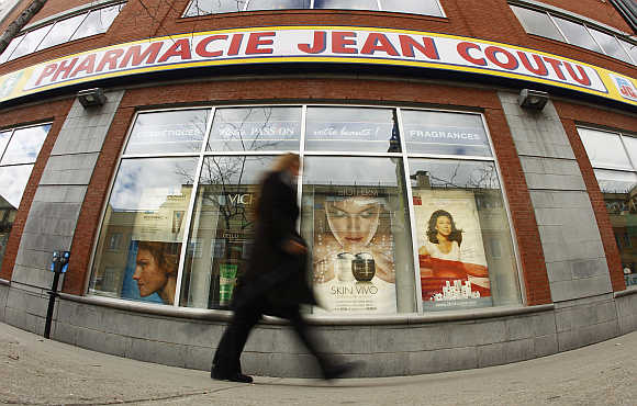 A pedestrian walks past a Jean Coutu pharmacy in downtown Montreal, Canada.