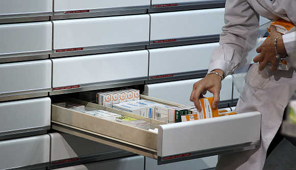 A chemist places medicines in a drawer at a pharmacy in Madrid, Spain.